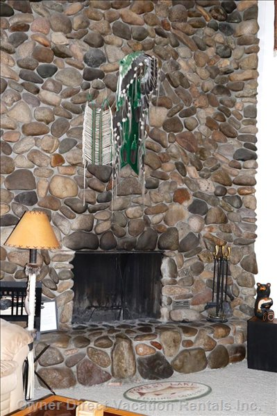 Dramatic River Rock Fireplace Rises 2-Stories to Vaulted Angled Wood Ceiling, Viewed from Kitchen