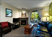 Living Area has a Leather Couch, Fire Place and a Quiet Deck with Mountain Views.