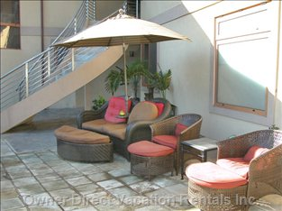 Upholstered Chairs and Umbrella in the Shaded Area of the Pool