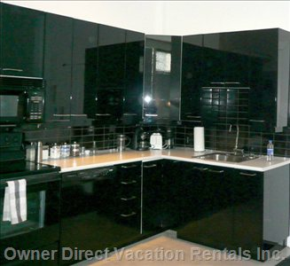 Kitchen - all Cabinets Are in Black Lacquer with Tinted Glass Doors. the Appliances Have a Black Lacquer Finish : Jenn-air Dishwasher, Jenn-air Cook Top and Wall Mount Oven, and Refrigerator. There Are Stainless Trim Accents and Probably Stainless Counters. Wall Back Splashe is Shiny Black Subway Tiles. this Will be a Serious Kitchen Look.