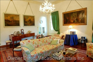 The Living Room has Six Windows on Three Sides and is Furnished with a Big Sofa, Two Easy-Chairs, Four Arm-Chairs and a Chaise Lounger.