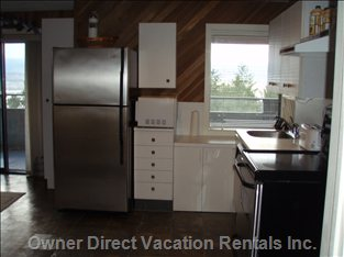 Kitchen with Stainless Steel Appliances, Slate Floor, View Window & Sliding Door to Deck